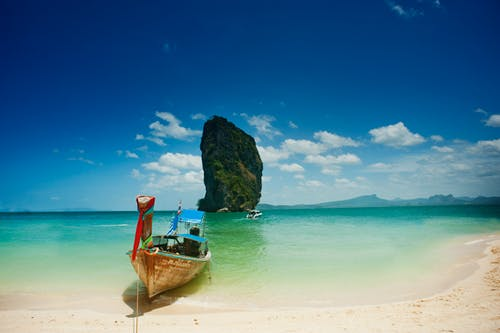 A person sitting on a beach near a body of water with Ko Poda in the background